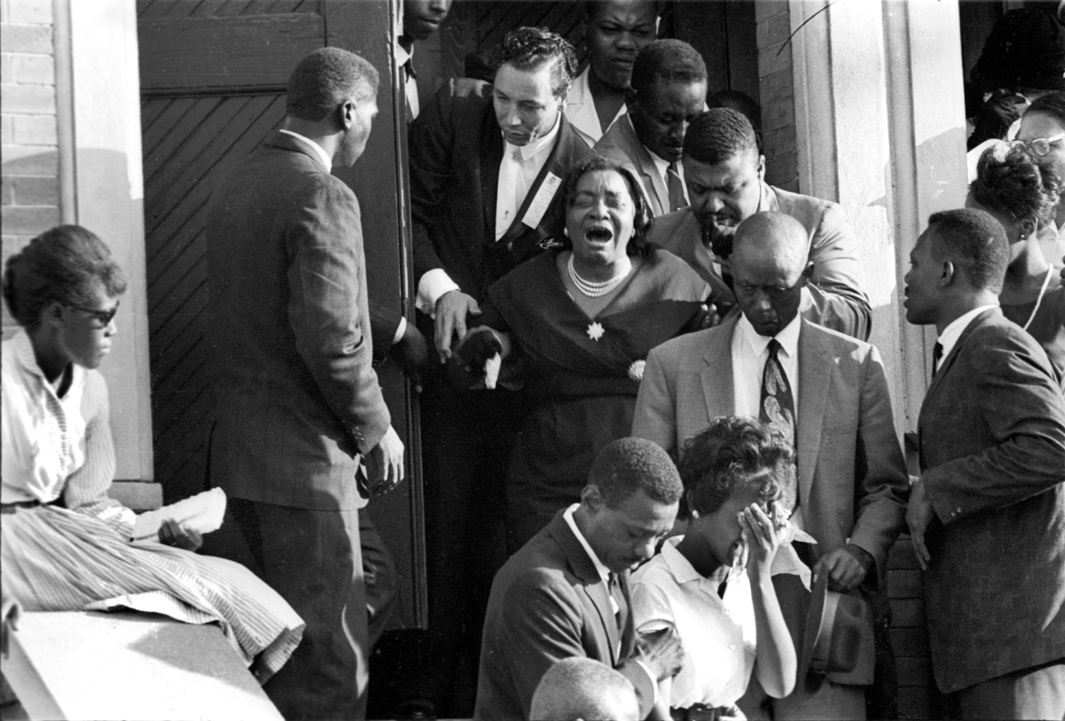 A woman, accompanied by a number of other people, sobs as she exits a funeral for victims of the 16th Street Baptist Church bombing in Birmingham, Alabama, 1963. The September 15, 1963 bombing killed four young African American girls. (Photo by Declan Haun/Chicago History Museum/Getty Images)